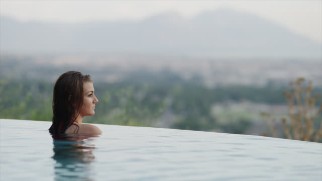 medium shot of teenage girl relaxing in infinity pool / cedar hills, utah, united states - infinity pool stock videos & royalty-free footage