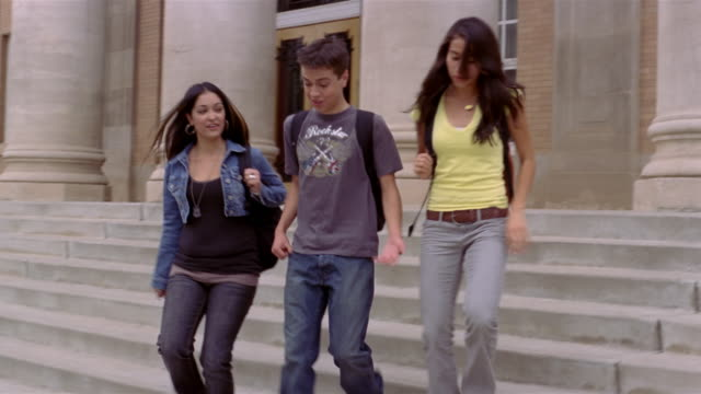 vidéos et rushes de medium shot of teenage girls and boy walking down steps together - teenage girls