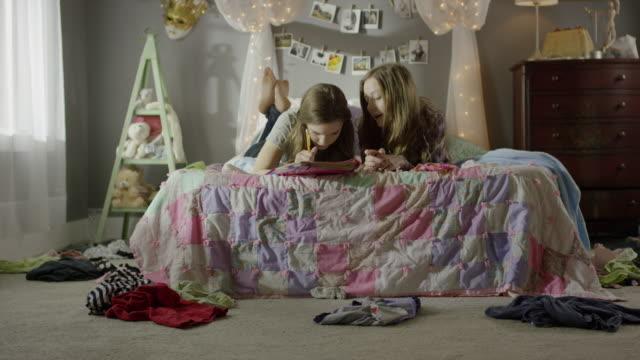 """medium shot of teenage girls doing homework on bed / cedar hills, utah, united states"" - legs crossed at ankle stock videos and b-roll footage"