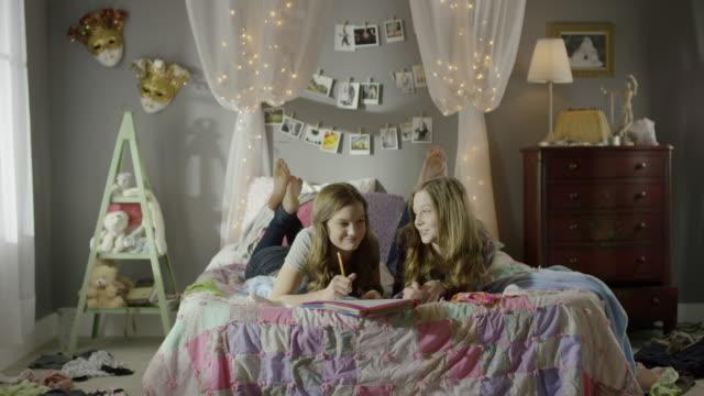 """medium shot of teenage girls doing homework on bed / cedar hills, utah, united states"" - only teenage girls stock videos and b-roll footage"