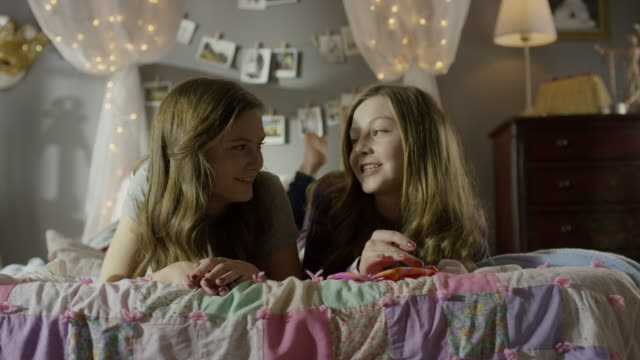 """medium shot of teenage girls laughing on bed / cedar hills, utah, united states"" - only teenage girls stock videos and b-roll footage"