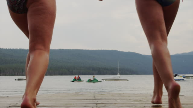 medium shot of teenage girls on dock running and jumping into lake / redfish lake, idaho, united states - 14 15 years stock videos and b-roll footage
