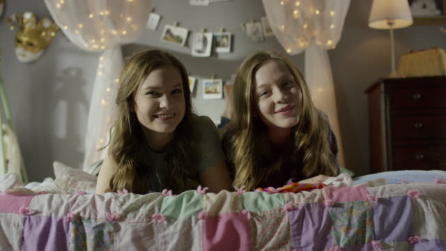 """medium shot of teenage girls smiling on bed / cedar hills, utah, united states"" - teenagers only stock videos and b-roll footage"