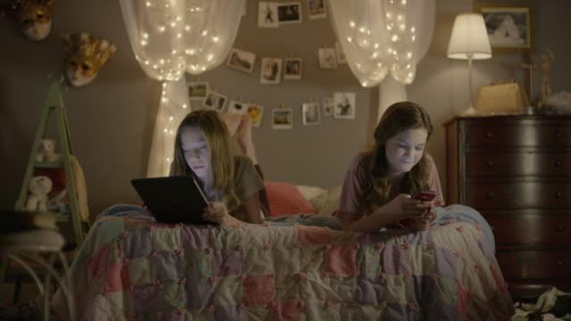 """medium shot of teenage girls using technology in bedroom / cedar hills, utah, united states"" - nur teenager stock-videos und b-roll-filmmaterial"