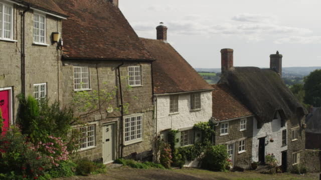 Medium shot of thatched-roofed houses in English village / Gold Hill, Shaftsbury, England, United Kingdom