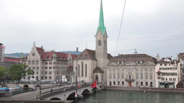 medium shot of the fraumunster church over the limmat river in zurich, switzerland - kirchturmspitze stock-videos und b-roll-filmmaterial