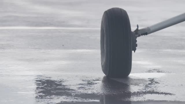 vídeos de stock e filmes b-roll de medium shot of the landing gear of an airplane in the rain - alfalto