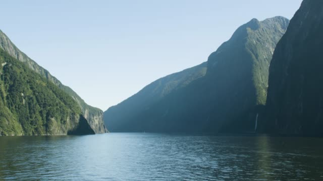 vidéos et rushes de medium shot of the milford sound with the stirling waterfall on the left - nouvelle zélande
