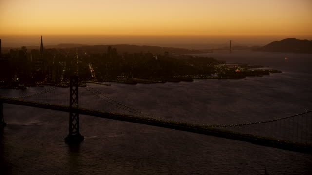 medium shot of the san francisco-oakland bay bridge with downtown san francisco in the background at dusk - north beach san francisco stock videos and b-roll footage