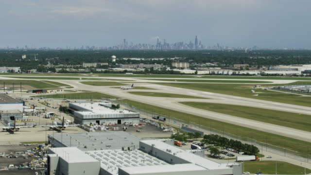medium shot of the taxiway of the o'hare international airport with downtown chicago in the background - taxiway stock-videos und b-roll-filmmaterial