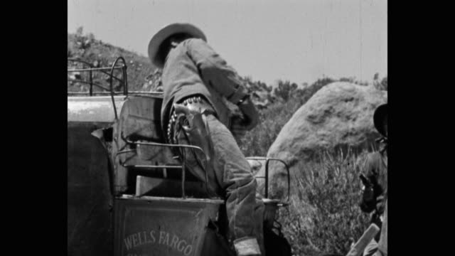 medium shot of thief shooting stagecoach driver with gun on dirt road - tod stock-videos und b-roll-filmmaterial
