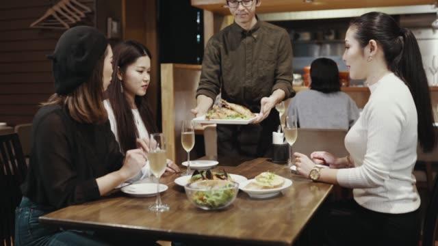 レストランでウェイターから食事を得る3人半ばの成人女性のミディアムショット - 若い女性点の映像素材/bロール