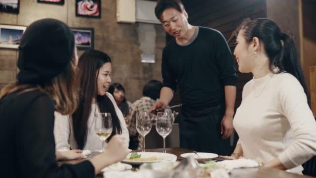Medium shot van drie mid volwassen vrouwen betalen voor maaltijd in een restaurant met behulp van een creditcard