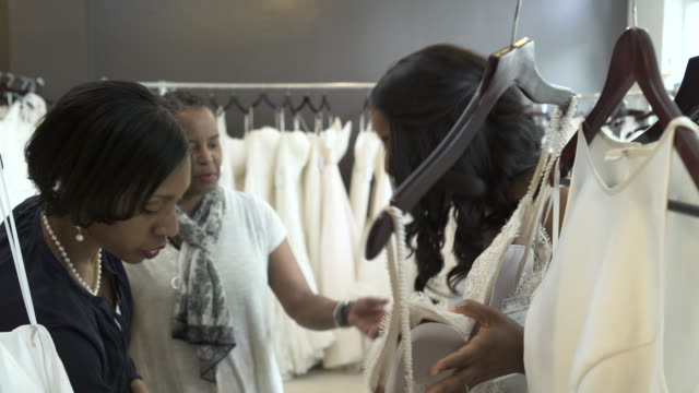 medium shot of three women looking at wedding dresses - wedding dress stock videos and b-roll footage