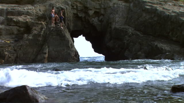 Medium shot of three young boys floating on water under a sea arch Big waves crashing on a rocky shore Zoom out Wide angle view of the sea arch Young...