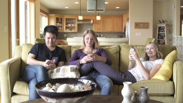 Medium shot of three young people texting in a room
