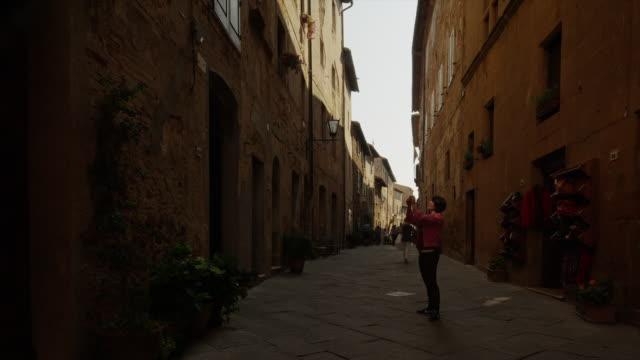 medium shot of tourist taking photographs in italian alley / piensa, tuscany, italy - 路地点の映像素材/bロール