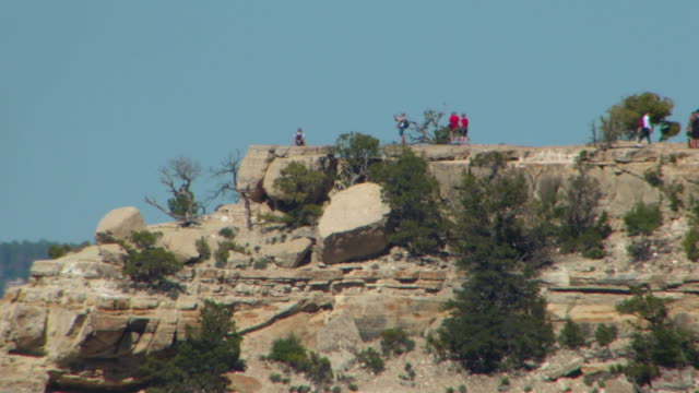 medium shot of tourists walking near the edge of the grand canyon south rim on april 24, 2019 in arizona. - grand canyon national park stock videos & royalty-free footage