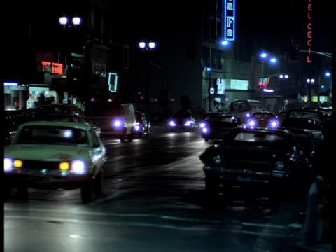 A medium shot of traffic at night streaming along a city street.