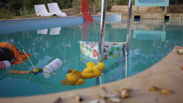 """ medium shot of trashed swimming pool in theme park"" - ぬいぐるみ点の映像素材/bロール"
