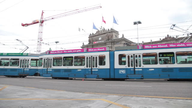 medium shot of trolleys passing in front of the zurich hauptbahnhof - male likeness stock videos & royalty-free footage