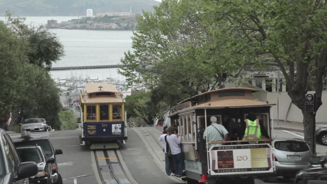 Medium Shot of trollies passing in San Francisco with Alcatraz in the background