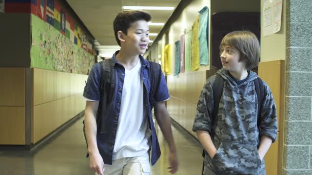 Medium shot of two friends talking in school corridor