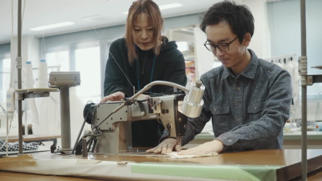 Medium shot of two mid adult design professionals working together in a textile manufacturing studio