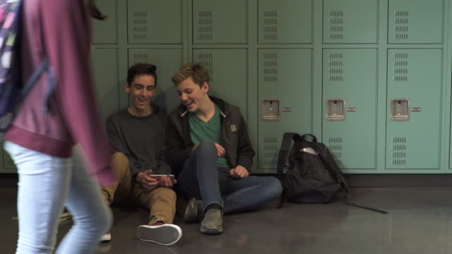 medium shot of two students showing phone to each other - spind stock-videos und b-roll-filmmaterial