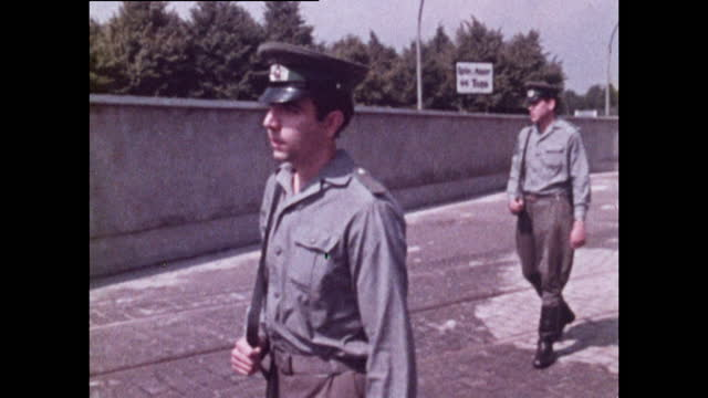 medium shot of two young policemen patrolling along the berlin wall in east berlin; 1970. - 20 29 years stock videos & royalty-free footage