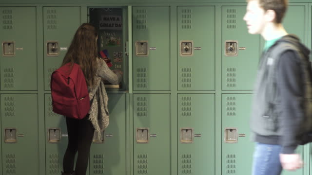 stockvideo's en b-roll-footage met medium shot of two young student packing in a locker while a friend arrives - lockerkast