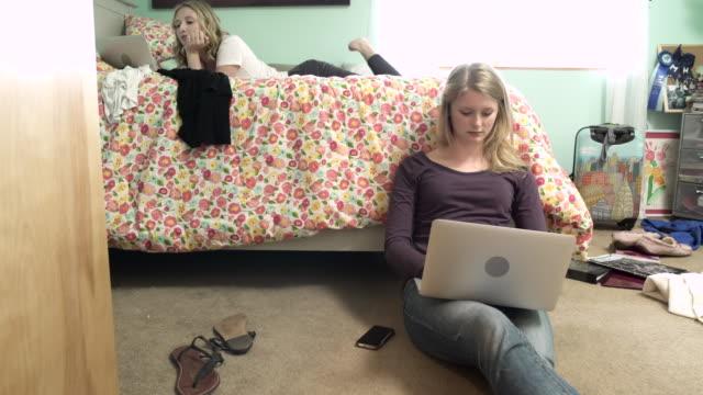medium shot of two young women using computers in a bedroom - auf dem boden sitzen stock-videos und b-roll-filmmaterial