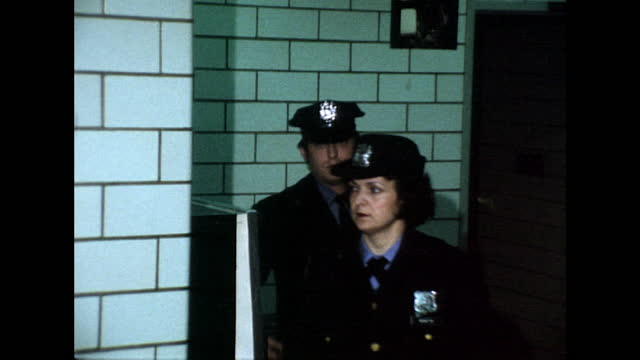 medium shot of uniformed police men and women exiting a doorway in file inside a new york police department station; 1975. - waist up stock videos & royalty-free footage