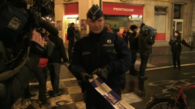 stockvideo's en b-roll-footage met medium shot of uniformed policemen unrolling blue and white police tape to block the street in belgium during lockdown and police raids after paris... - (war or terrorism or election or government or illness or news event or speech or politics or politician or conflict or military or extreme weather or business or economy) and not usa