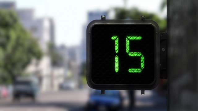 medium shot of walk signal with a green display as it shows a 15 second countdown with traffic in the background - semaforo video stock e b–roll
