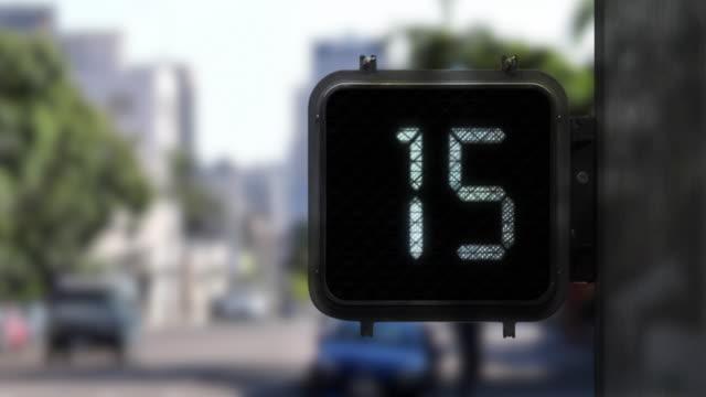 vidéos et rushes de plan moyen de signal de marche avec un affichage blanc pendant qu'il montre un compte à rebours de 15 secondes avec le trafic en arrière-plan - instrument de mesure du temps