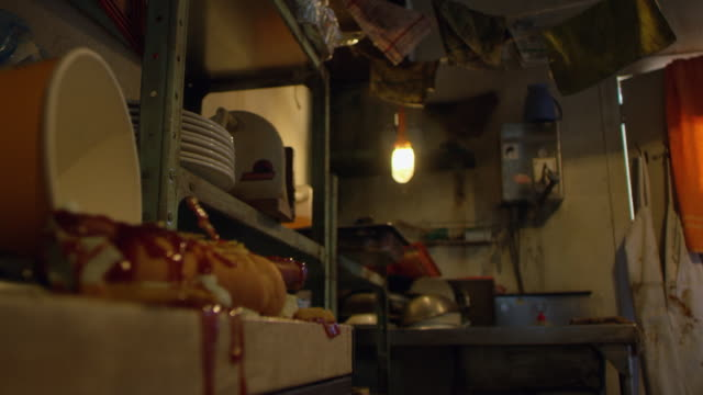 """"""" medium shot of water dripping from wet napkin with food in foreground in workshop/garage"""" - 電球点の映像素材/bロール"""