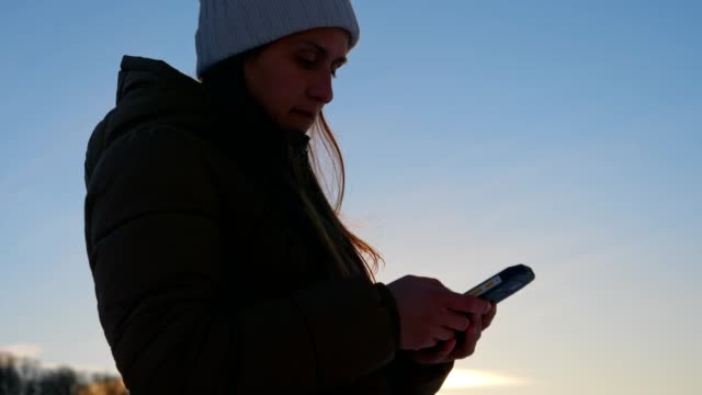 vídeos de stock e filmes b-roll de medium shot of winter traveler at sunset using smartphone, close up of one young woman tourist using internet, chatting, enjoying the winter mountain, portrait, winter sport, travel, exploration, adventure, tourism, outdoors, mountain hiking, - back lit