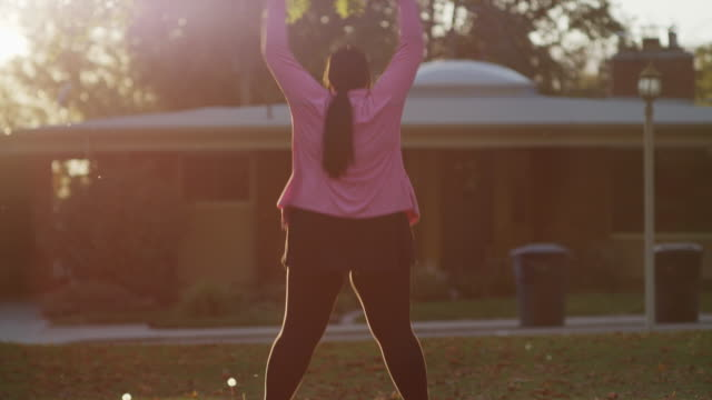Medium shot of woman doing jumping jacks on lawn / Orem, Utah, United States