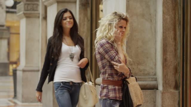 Medium shot of woman greeting friend in shopping mall / Milan, Italy