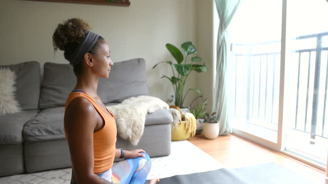 medium shot of woman in lotus position relaxing after working out in living room of home - lotus position stock videos & royalty-free footage