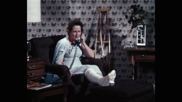 medium shot of woman in orthopedic cast talking on telephone at home - ギプス点の映像素材/bロール
