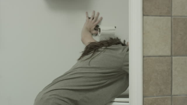 medium shot of woman kneeling and vomiting in toilet / springville, utah, united states - kneeling stock videos and b-roll footage