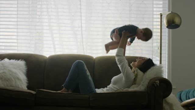 Medium shot of woman laying on sofa lifting baby son / Provo, Utah, United States