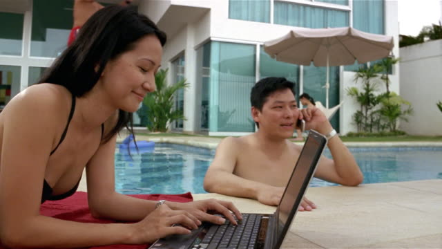 Medium shot of woman lying by swimming pool using laptop and man in pool alking on cell phone / boy and girl jumping into water / girl sitting at table in background