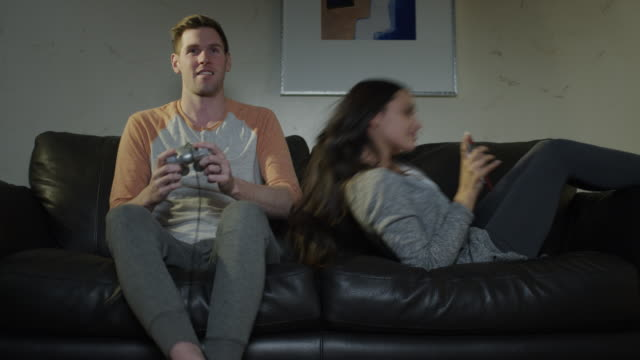 Medium shot of woman on sofa irritated at man playing video game / Cedar Hills, Utah, United States