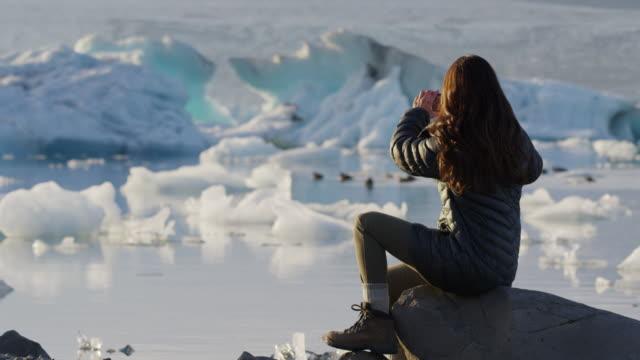 Medium shot of woman photographing ducks in glacier lagoon / Jokulsarlon, Iceland