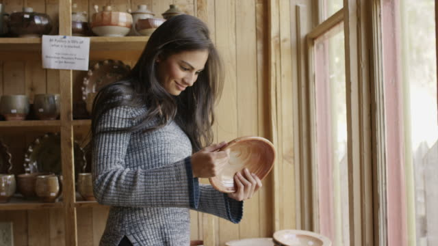 Medium shot of woman shopping for bowl in pottery store / Spring City, Utah, United States