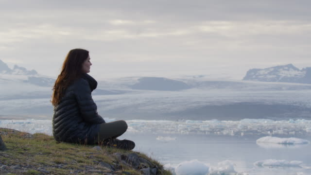 medium shot of woman sitting on hill admiring glacier lagoon / jokulsarlon, iceland - admiration stock videos & royalty-free footage