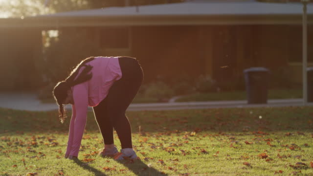 Medium shot of woman stretching on lawn / Orem, Utah, United States